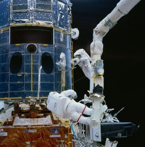 Jeff Hoffman (with red stripes on the legs of his suit) and Story Musgrave work on the Hubble Space Telescope. Photo Credit: NASA