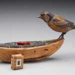 "Image of the artiwork titled ""sentinella"" with a wooden boat filled with metal type, a wooden bird, and a small book with a coptic binding"