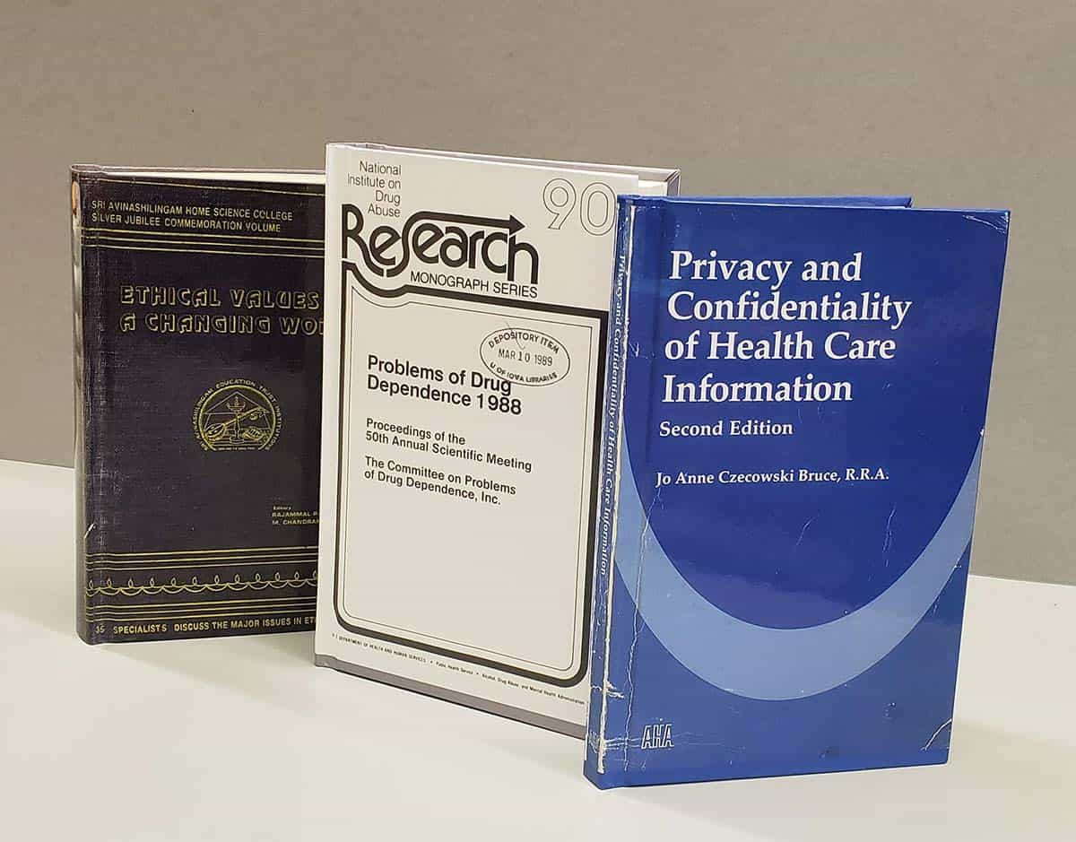 Three books with digitized images of their original cover printed on the new binding