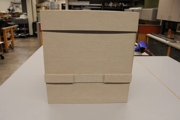 Closed box with lid on top and a strap securing the middle.