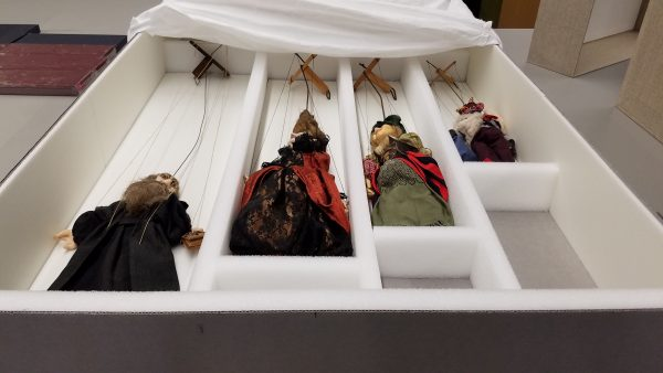 A large box container four marionettes in separate foam compartments.