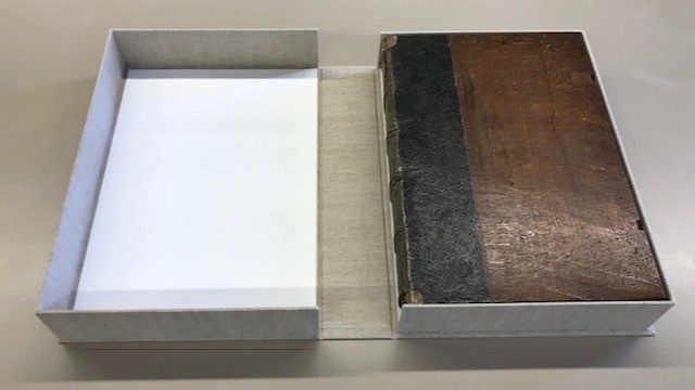 A cloth-covered box lying open to show the rare book housed within.