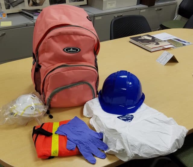 Pictures shows a pink backpack with items sitting in front of it. These items are a hard hat, Tyvek suits, gloves, a safety vest, and respiratory masks.