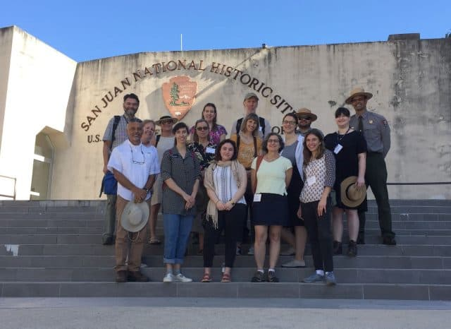 Pagan (first row, second from the left) and other participants stand in front of the San Juan National Historic Site for a group photo.