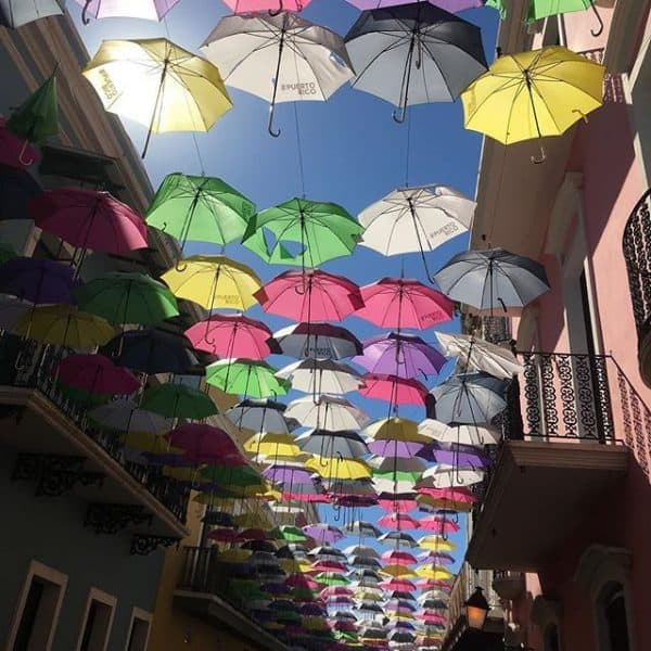 Colorful umbrellas hanging from wire about Foraleza Street.