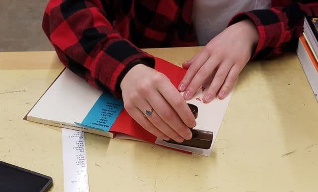 A Library Marking student employee is property stamping the front inside cover of a new book.