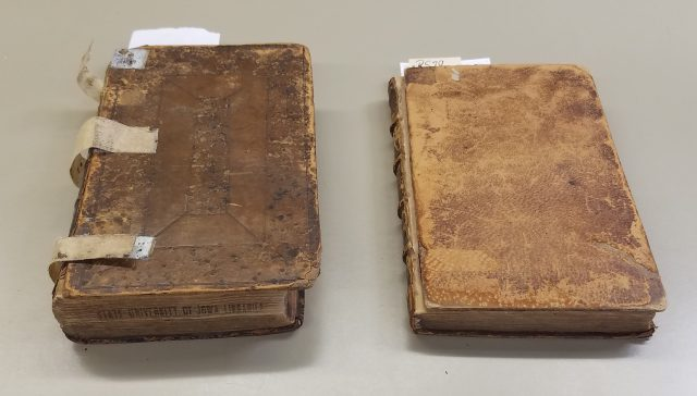 There are two books. The one on the left has a front cover that is bigger than the textblock and the one on the right has a cover where the leather is lighter than the spine and back cover.