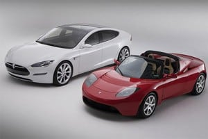 The Tesla Model S electric car next to the Tesla electric Roadster.