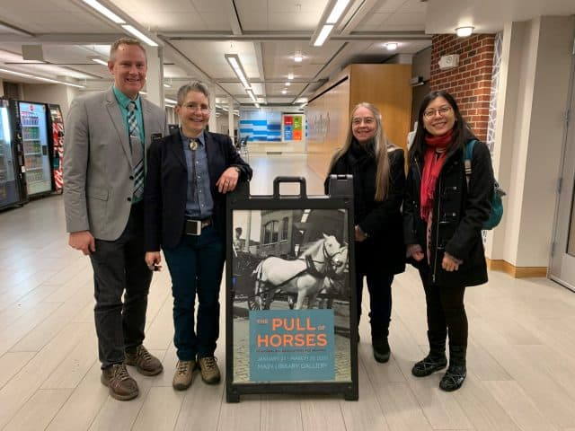 Mark Anderson, Kim Marra, Mary Bennett, and Hang Nguyen stand in a row, smilling, next to a poster of two white horses.