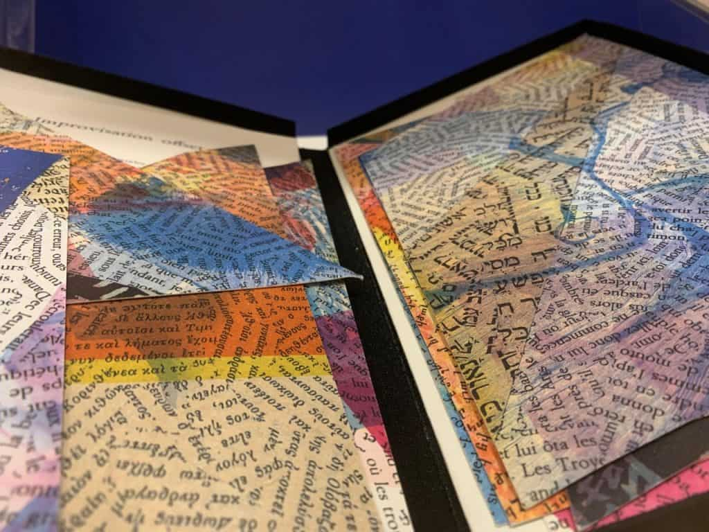 The image shows colorful papers in many sizes of triangular shapes covered in words from various languages.