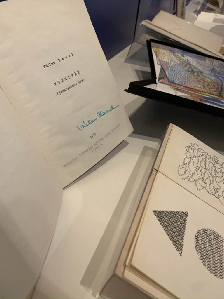 Two books are open inside a gallery case. One is signed by Vaclav Havel.