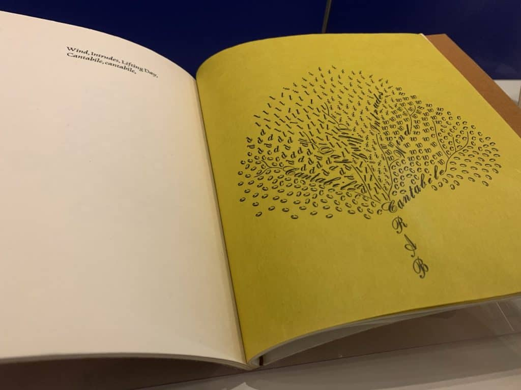An open book. One page is white and says: Wind, Intrudes, Lifting Day, Cantabile, cantabile. The opposite page is yellow. Those words and a slew of individual letters (C, I, L, R, A, D, W) take the shape of a tree with vibrant branches.