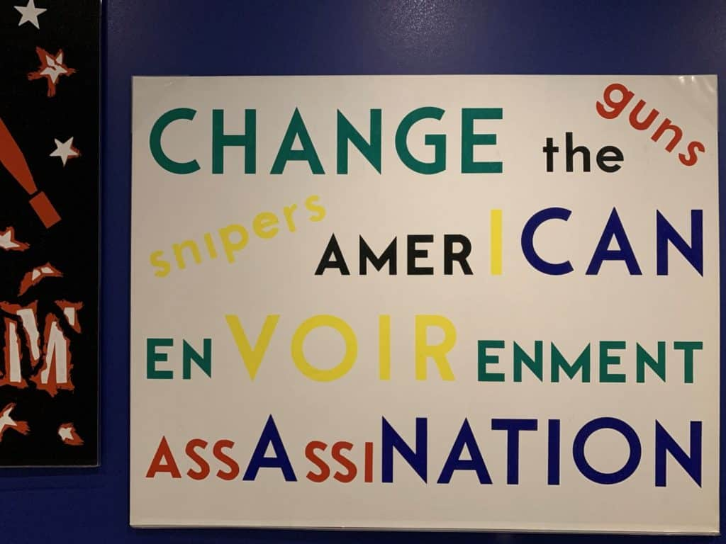 White poster with words in various sizes and primary colors. The words are: Change the American Environment. Guns. Snipers. Assassination.