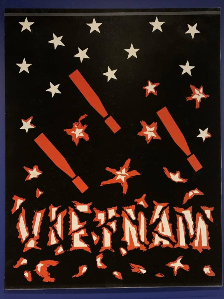 Poster with black background punctuated by falling white stars, small red explosions, and three bombs that look like exclamation points. At the bottom the text says Vietnam and appears wrapped in barbed wire.