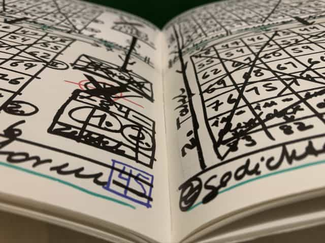 A book open to pages filled with hand drawn grids and numbers.