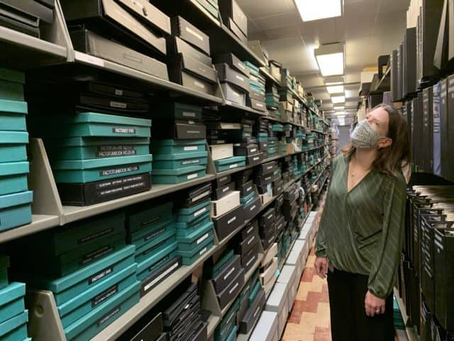 Margaret Gamm stands in an aisle between long bookstacks filled with black and teal document boxes.