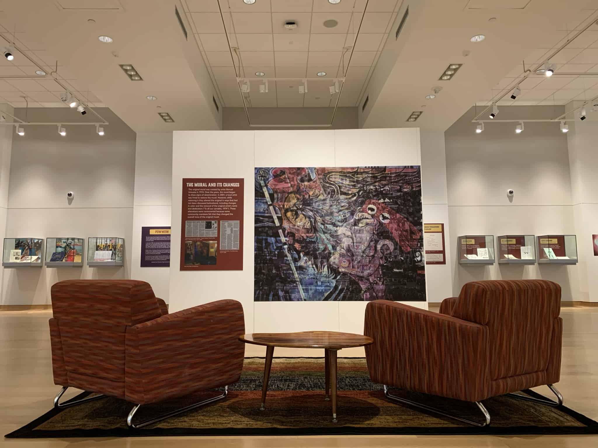 Two chairs face a mural and six glass cases filled with items from the Latino Native American Cultural Center.