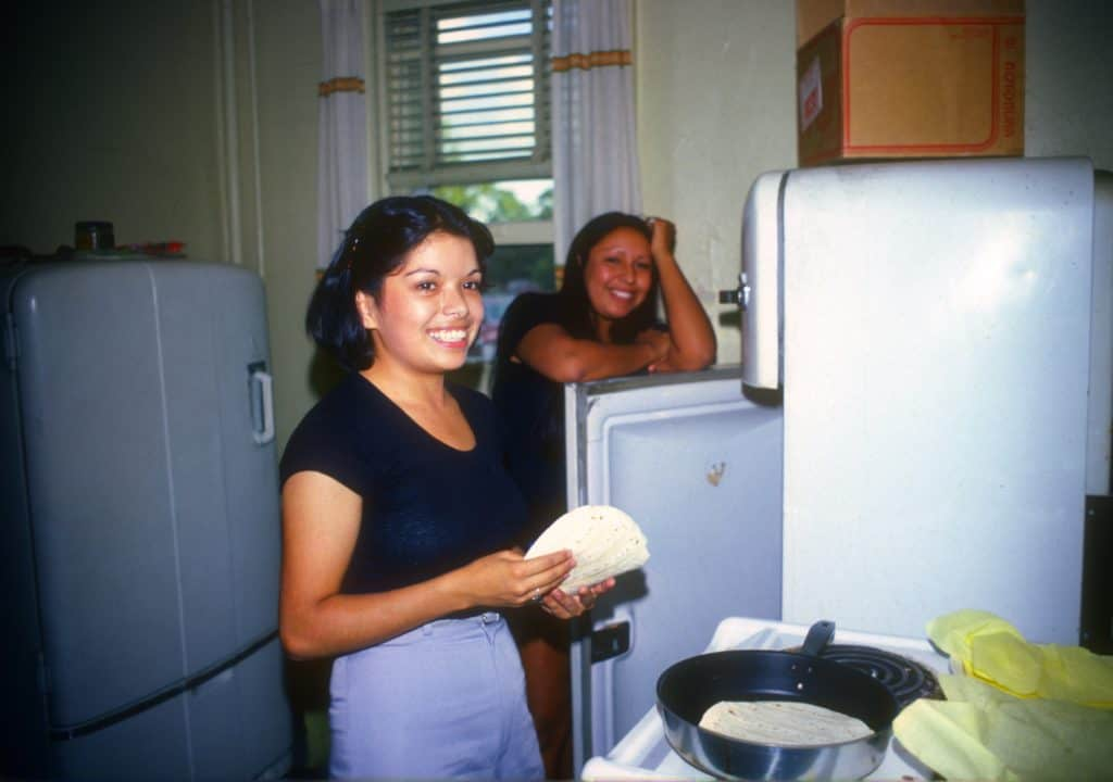 Two women are in the house kitchen. One woman is preparing tortillas.