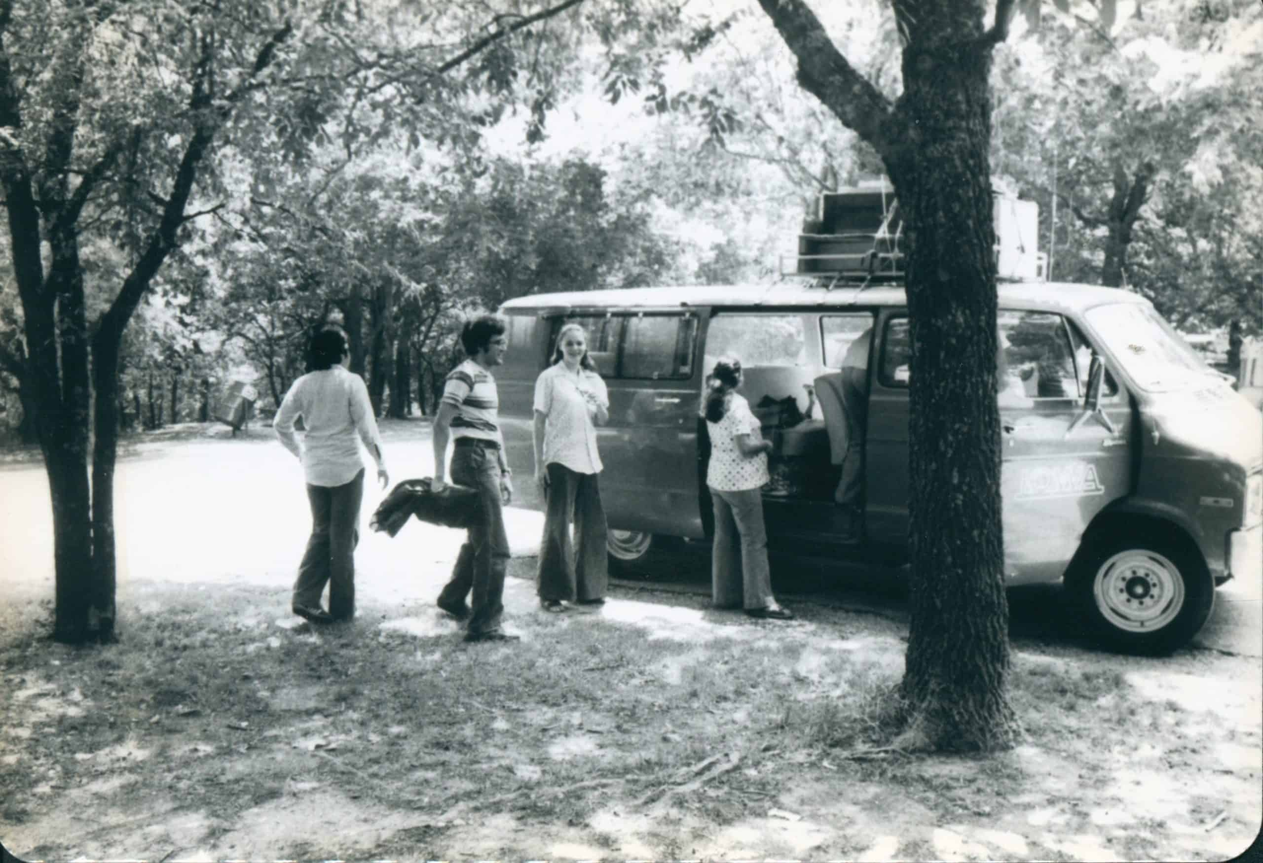 Black and white photo of students standing outside a van on the way to a performance.