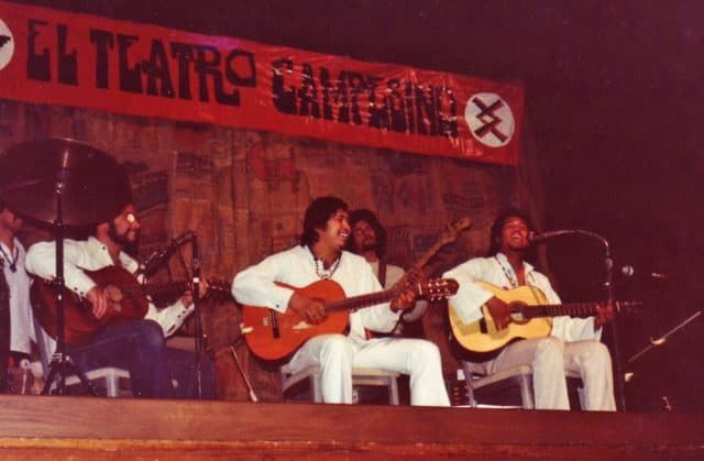 Five Latinx men in white shirts smile, sing, and play guitar on stage. A banner behind them says El Teatro Campesino.