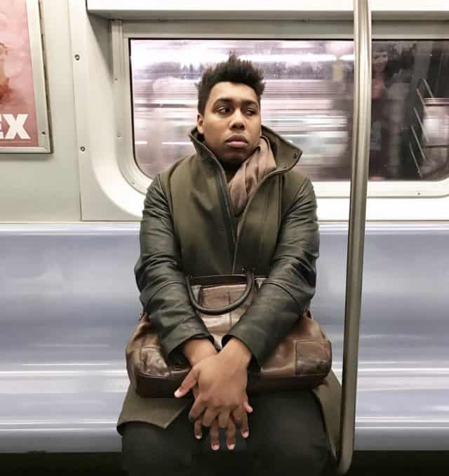 A portrait of Saeed Jones, a Black man who is sitting in a subway car and holding a satchel.