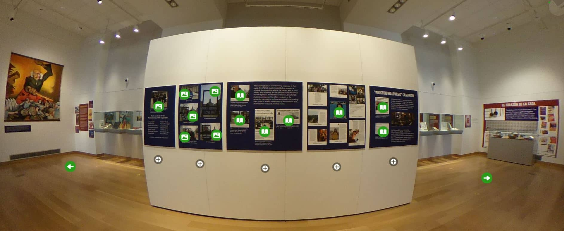 A panoramic view of part of the Main Library Gallery exhibit shows several text panels with clickable icons.