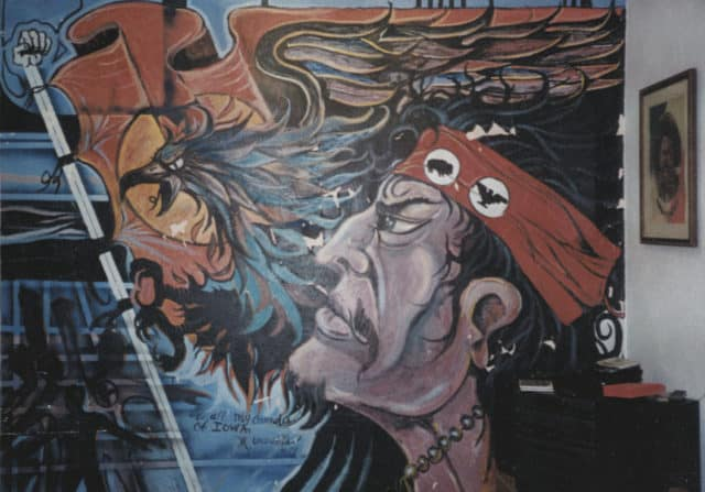 Original mural showing a Latinx man looking forward with determination. A flag and eagle are next to him, and he wears a headband that represents both Latino and Native American causes.