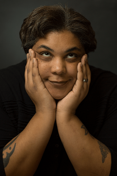 Black author Roxane Gay cups her face between her hands, elbows on the table in front of her. She looks up and she smiles, lips together.
