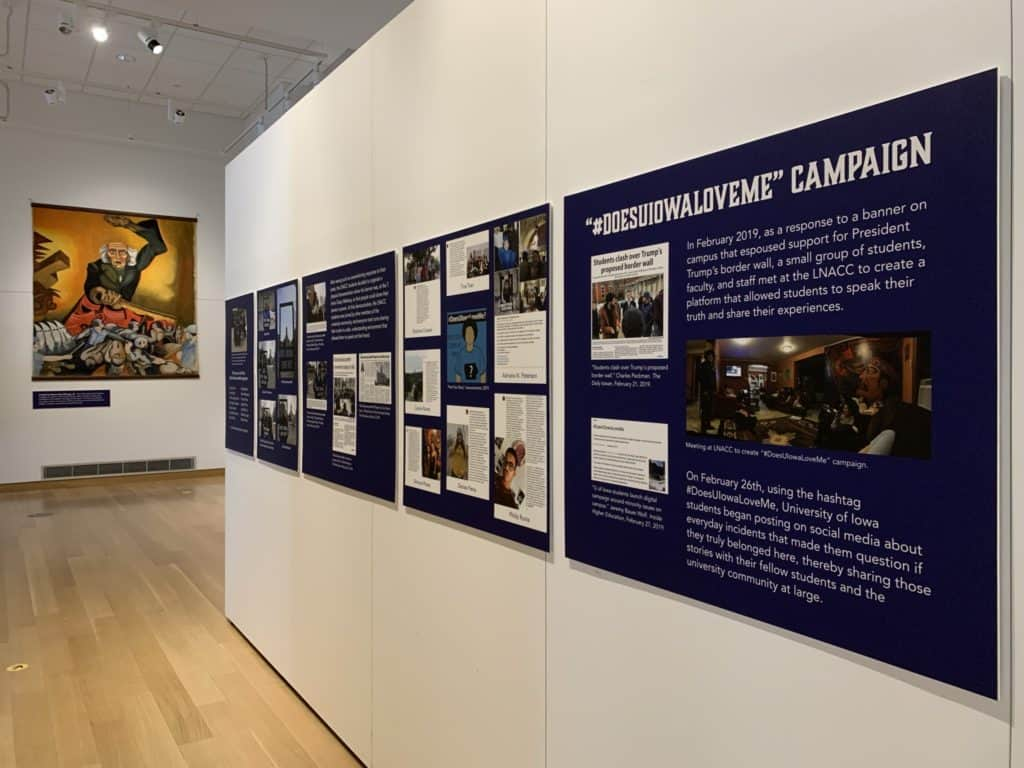 Blue text panels tell the story of the #DoesUIowaLoveMe campaign. A large canvas painting is seen in the background.