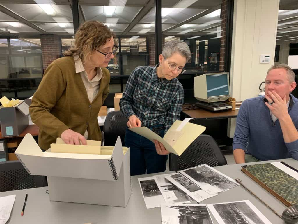 Three people look through archival files as they plan an exhibition for the Main Library Gallery.