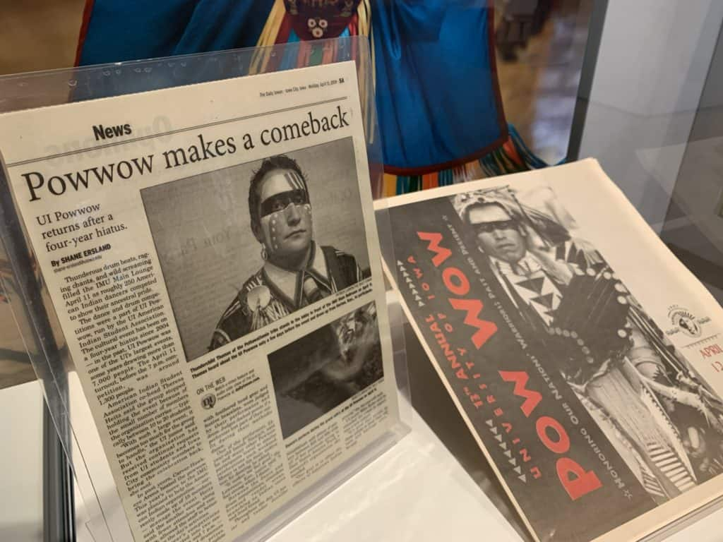 A laminated newspaper article about the University of Iowa Powwow and a printed program from a Powwow are on display together in a case.