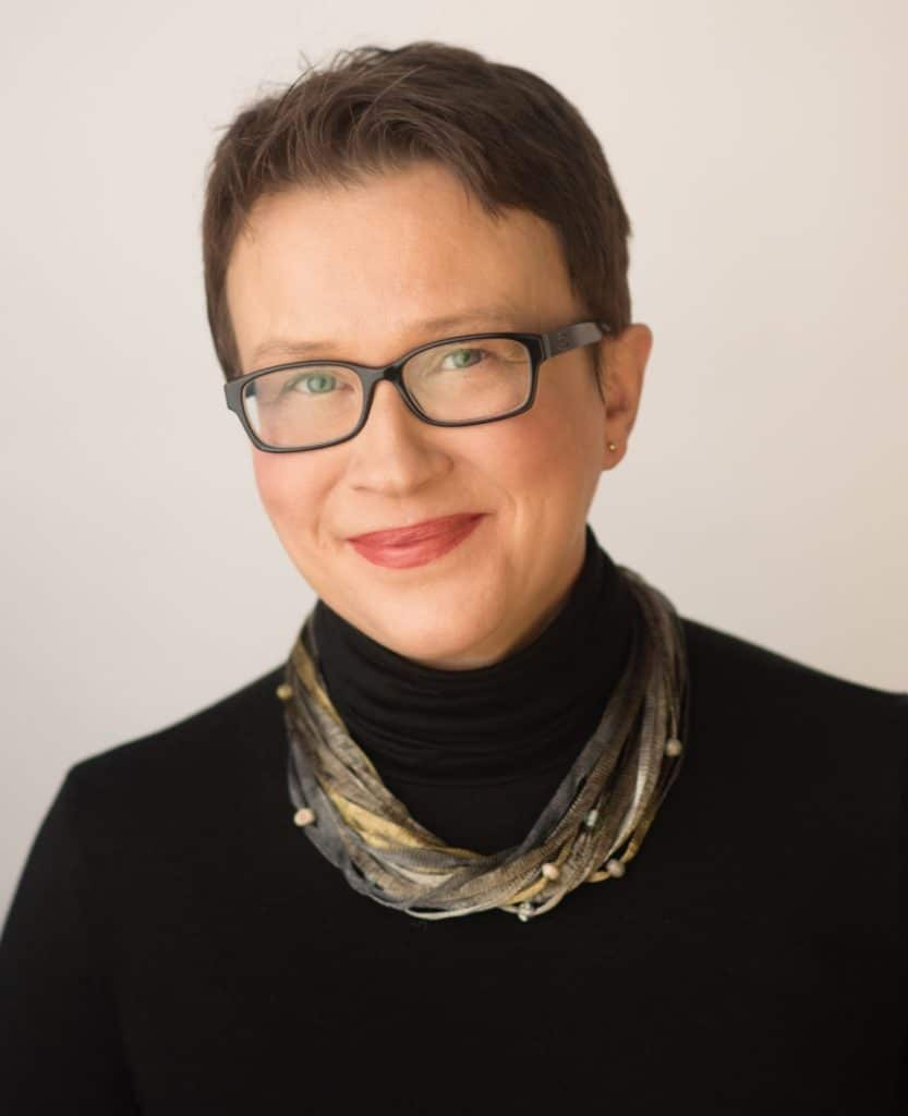 A portrait of Anna Barker. She is a white woman with short dark hair and glasses.
