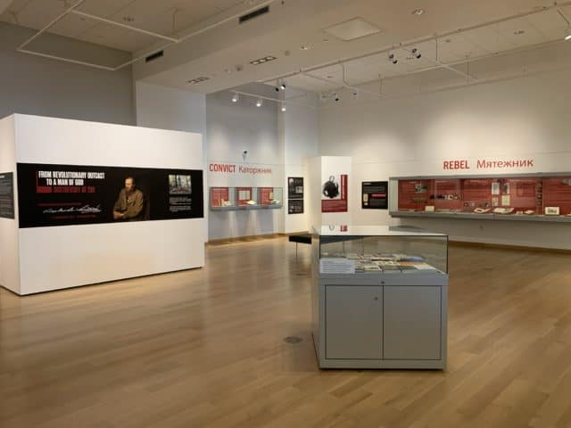 Wide view of the Main Library Gallery featuring a poster with the exhibit title on it. Cases hold books and other objects for display.