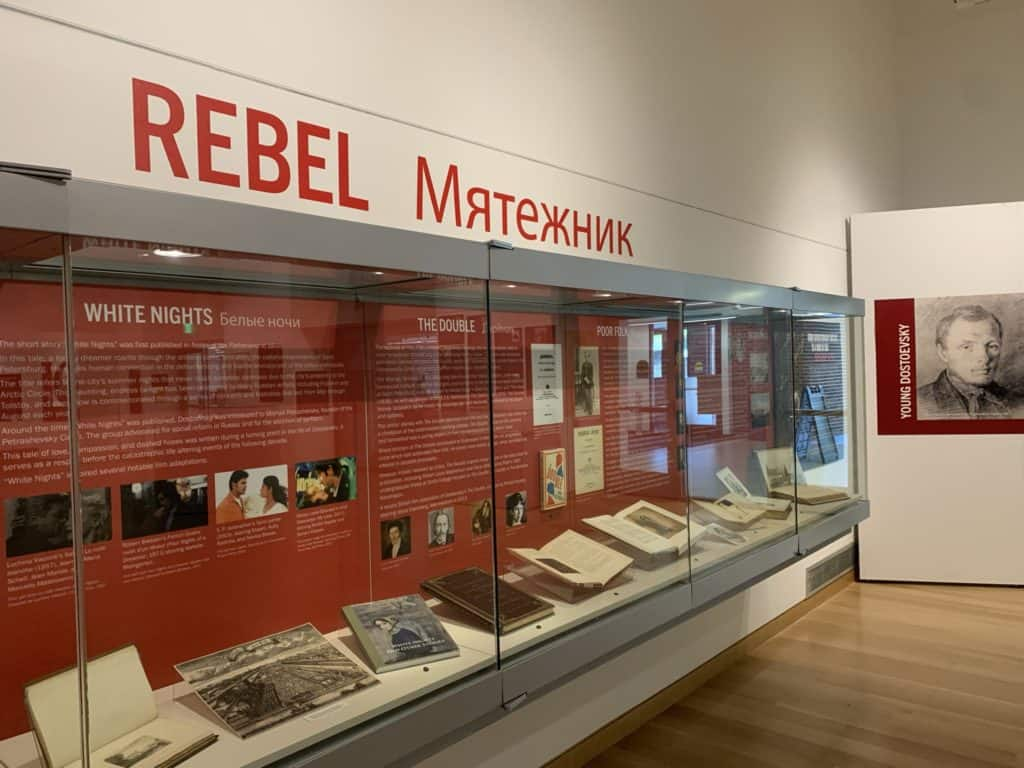 An exhibit case is filled with books and informational panels. Above the case is the word Rebel. A portrait of young Dostoevsky is in the background.