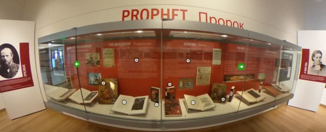 An exhibit case is filled with books and text about the objects on display.