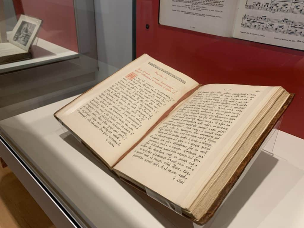A Russian psalter is open and displayed in an exhibit case.
