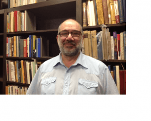 image of white man with glasses standing in front of bookcases