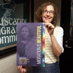 Janet Weaver holding a Migration is Beautiful poster