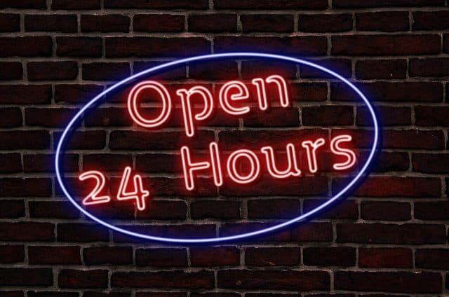 open 24 hours sign on brick wall