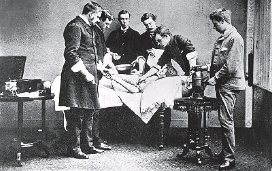picture of 6 men around a surgical patient
