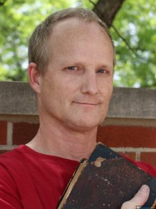 image of Duncan Stewart, white man, holding book in front of brick wall