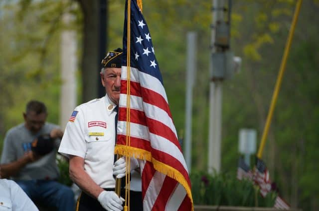 image of white man with flag, wearing honor guard uniform, carrying flag