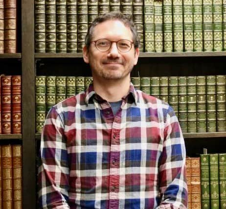 photo of Damien Ihrig, white man, in front of a bookcase