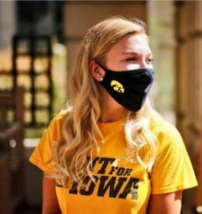 young woman, blonde hair, yellow shirt, black face mask with tigerhawk logo
