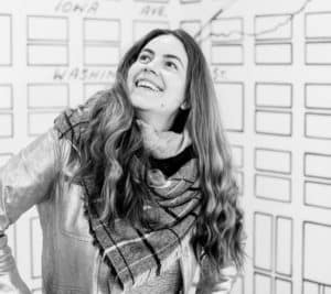 black and white image of Vero Rose Smith, white woman wearing scarf in front of map of Iowa City by Christopher Hunter