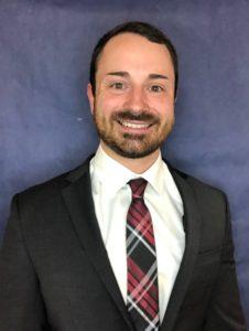 head shot photo of Joe Promes, white man, beard and mustache, black suit, tartan tie