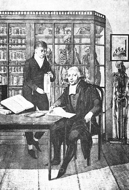 black and white image of Jan Bleuland with another person in room with books and skeletons