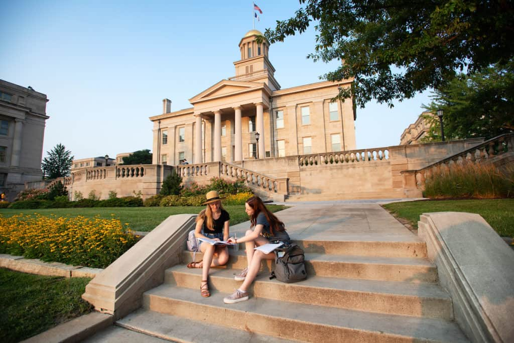 2 women sitting on steps with old capital in background