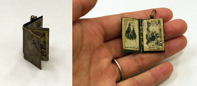 Miniature metal book with hinges and pages that turn.