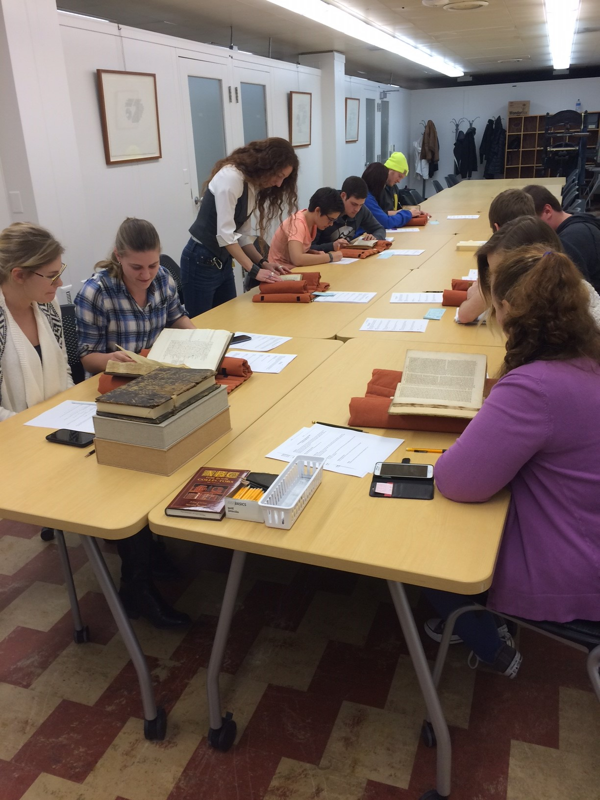 Image of a class of students examining books